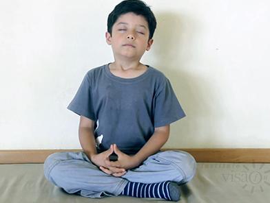Criança meditando sentada de frente e de olhos fechados