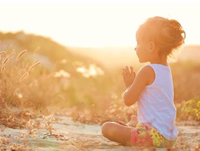 Criança meditando ao ar livre com a luz solar ao fundo