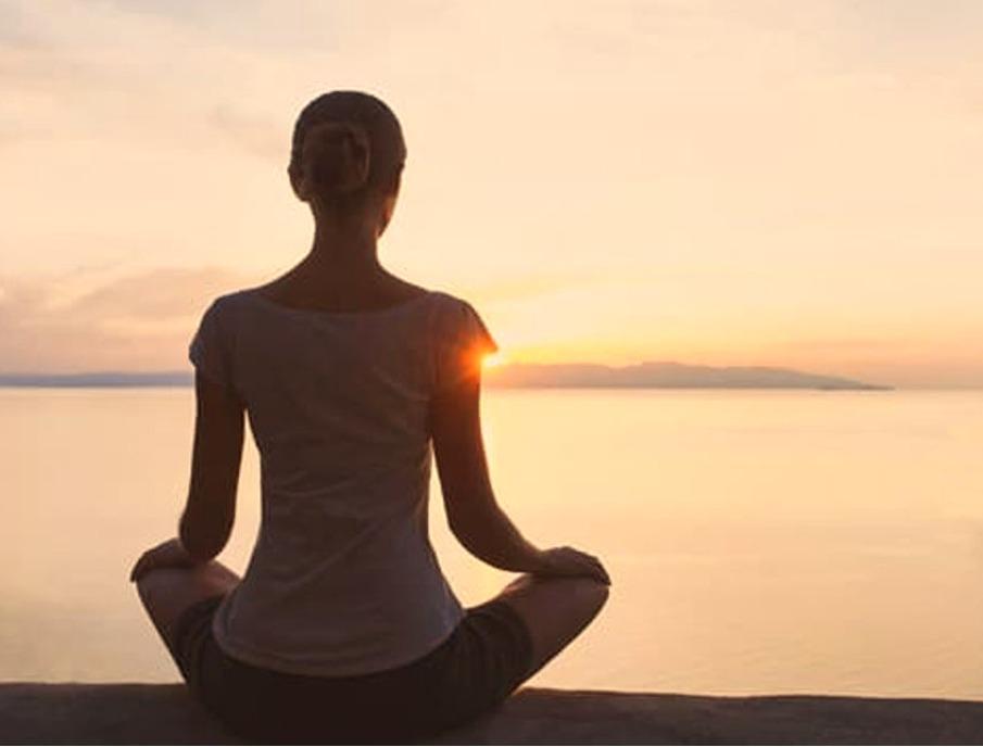 Mulher de costas meditando olhando para o horizonte